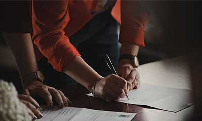 Person signing a paper on a desk with another person standing next to them
