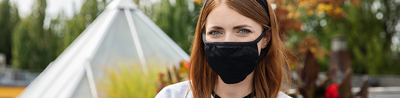 Photo of a young woman with shoulder length red hair and a light grey sweater wearing a black face mask and looking directly at the camera