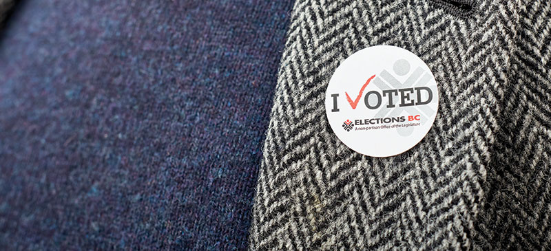 An I Voted sticker on a blue sweater